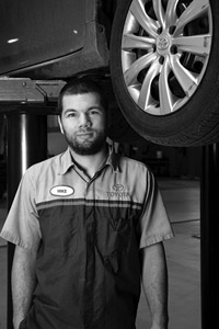 a grey scale photo of a man next to a car on a lift, he is wearing a mechanic's shirt