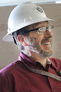 man wearing a white hard hat is shown in profile, he is smiling