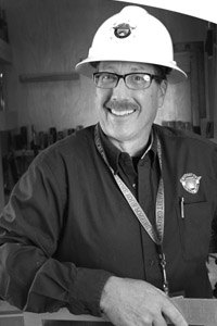 greyscale image of a man in a hard hat smiles at the camera