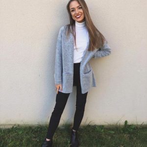 Girl standing in front of a plain wall smiling