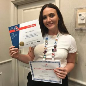 Girl holding certificates up and smiling